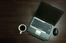 Typisches Arbeitsgerät: Laptop und eine Tasse Kaffee